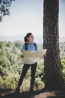 若い女性のバックパッカーのハイカー読書地図ハイキング旅行。休日にリラックスしてください。