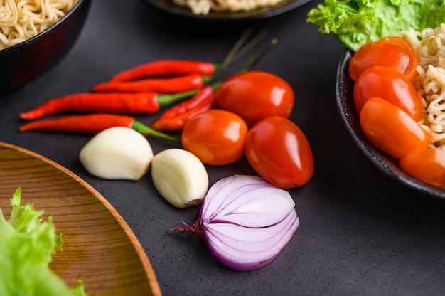 Яркий крупный план кусочков красного лука, чеснока, помидоров и перца. выборочный фокус