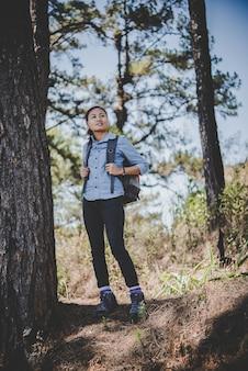 ヤングハイカーの女性は山にハイキングしながら休憩。冒険の休日のコンセプト。
