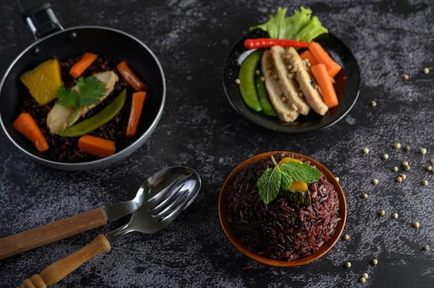 Фиолетовые рисовые ягоды, приготовленные на гриле с куриной грудкой тыквенные морковные листья листья мяты в блюдо и ложку, вилку, чистую еду.