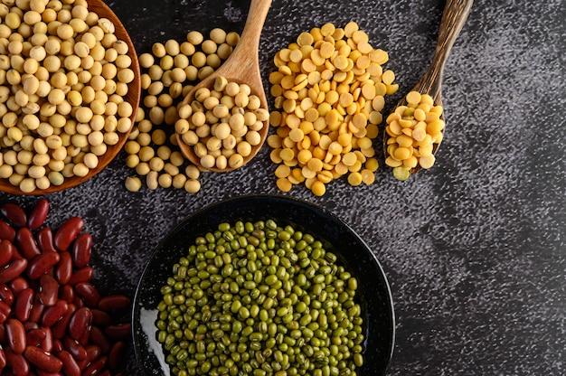 マメ科植物、および黒いセメントの床での豆の品揃え。