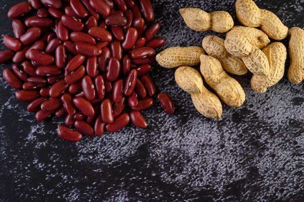 Арахис и красная фасоль на черном цементном полу.