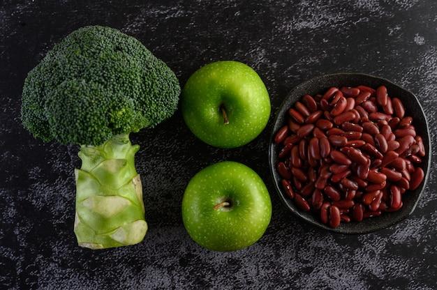黒いセメントの床にブロッコリー、リンゴ、小豆。