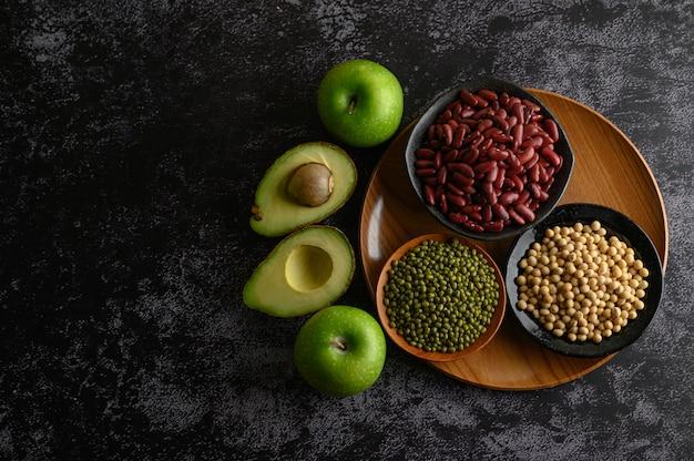 黒いセメントの床にマメ科植物と果物。
