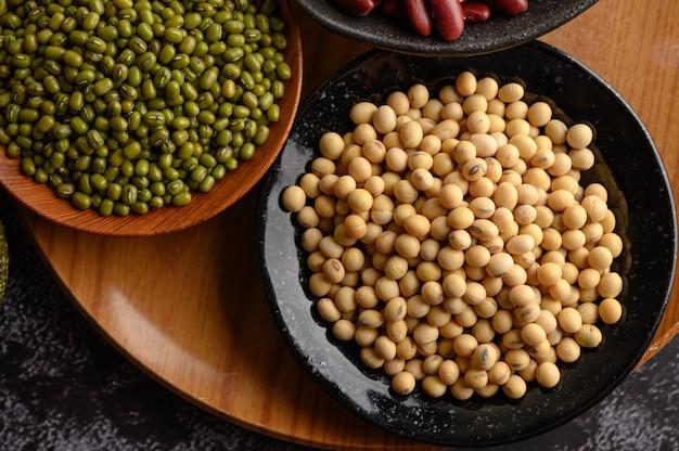 黒いセメントの床のプレート上の緑豆と大豆。