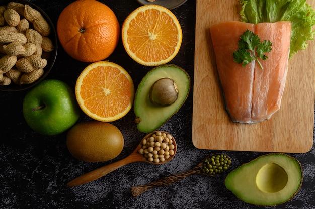 木製のまな板の上のマメ科植物、果物、およびサケの魚片。