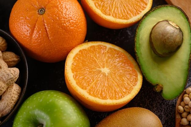 新鮮なオレンジアップル、キウイ、ピーナッツ、アボカドのスライスでクローズアップ。
