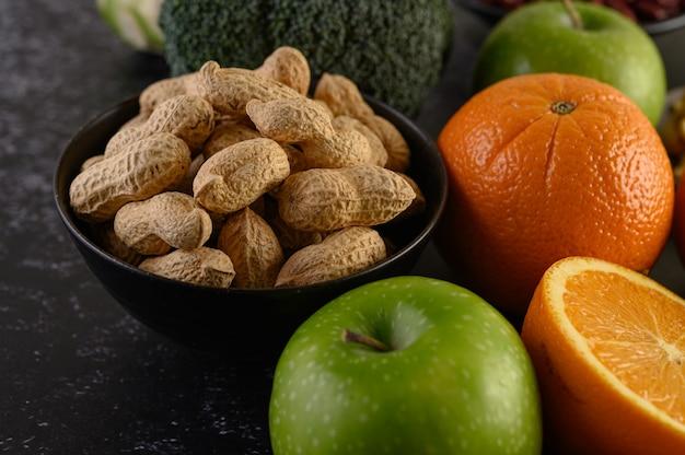 ピーナッツ、新鮮なオレンジのスライス、リンゴ、キウイ、アボカドでクローズアップ。