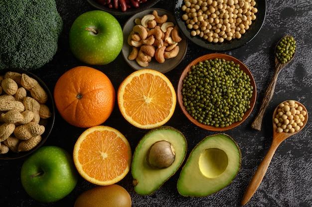 Бобовые и фрукты на черной цементной поверхности пола.