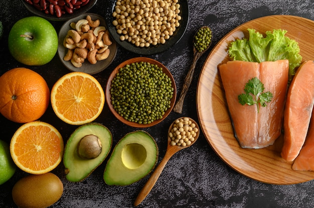 木の板にマメ科植物、フルーツ、サーモンの部分。