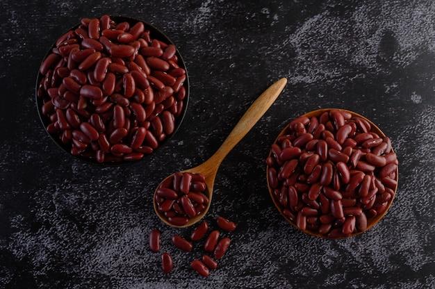 Красная фасоль в деревянной миске и деревянной ложкой на черном цементном полу.