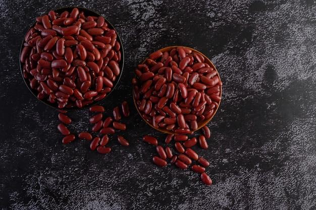 Красная фасоль в деревянной миске на черном цементном полу.