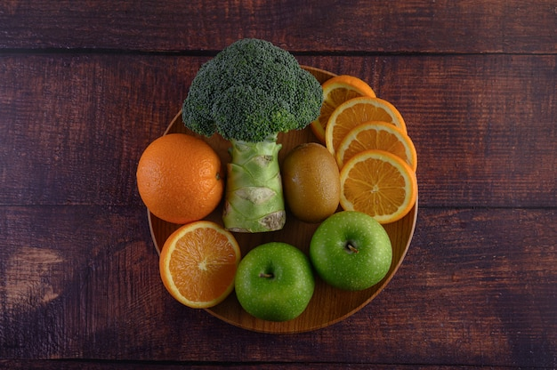 木の板にオレンジ色の部分、リンゴ、キウイ、ブロッコリー。