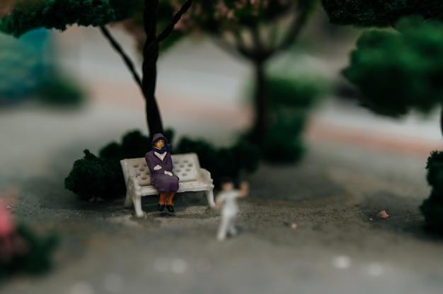 公園の椅子に座っている小さな人々のクローズアップ。