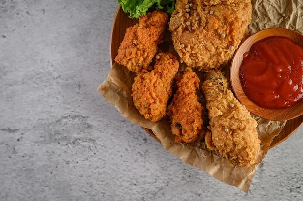 Хрустящая жареная курица на деревянной тарелке с томатным соусом