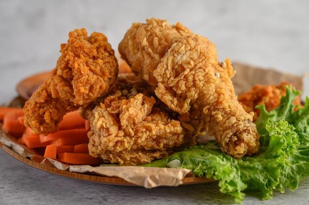 Хрустящая жареная курица на тарелке с салатом и морковью