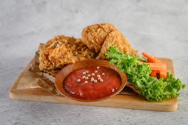 Хрустящая жареная курица на разделочной доске с томатным соусом
