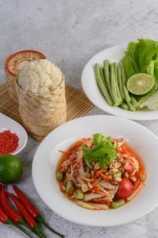 Тайский салат из папайи в белой тарелке с клейким рисом в плетеной корзине из бамбука и сушеными креветками