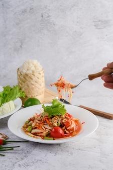 Тайский салат из папайи в белой тарелке с клейким рисом и сушеными креветками