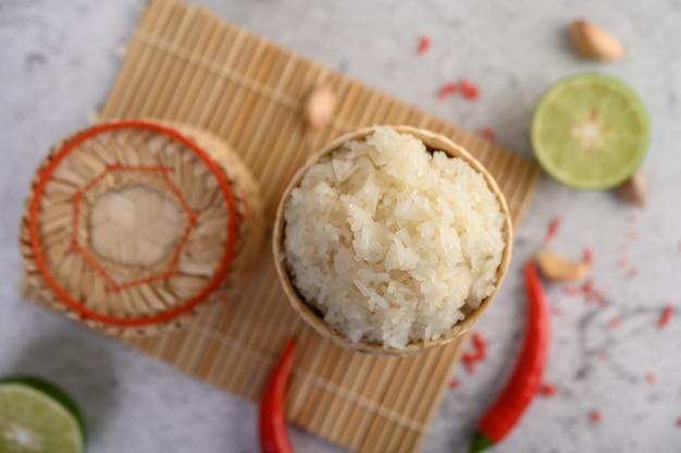 Тайский клейкий рис в плетеной бамбуковой корзине на деревянной панели с чили, лаймом и чесноком
