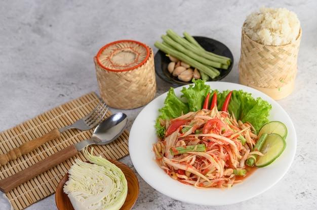 Тайский салат из папайи в белой тарелке с клейким рисом