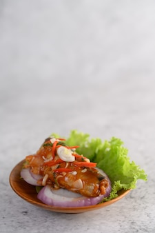 Аппетитный острый консервированный салат из сардины с острым соусом в деревянной миске