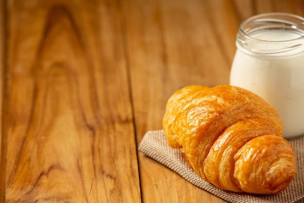 パンと牛乳、グラスに乗せ、古い木の床に乗せます。
