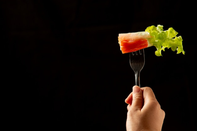 Тайский салат с чесноком на столовых приборах в руке