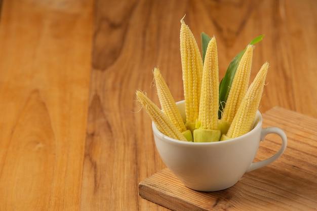 Детская кукуруза укладывается в стакан на деревянный пол.