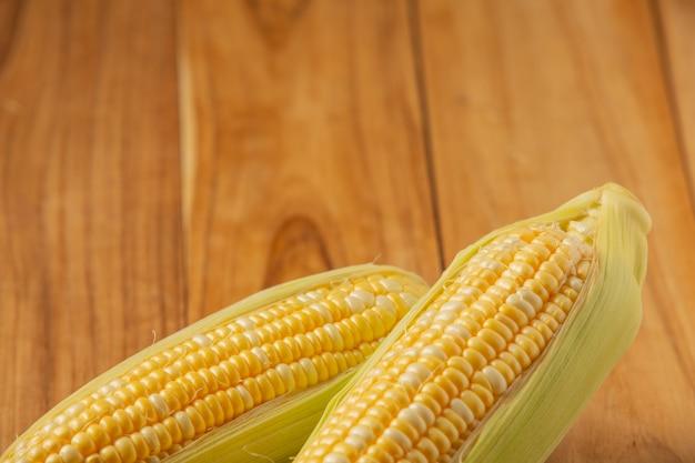Два кусочка кукурузы на деревянный стол.