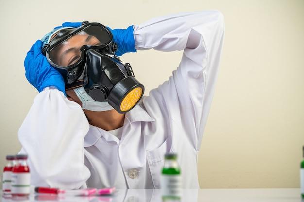 科学者はガスマスクを着て座って、頭に手を置いた