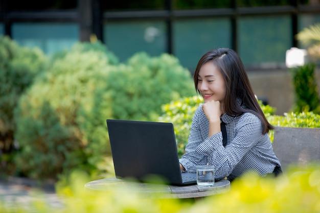Улыбается бизнесвумен, работает на ноутбуке в кафе