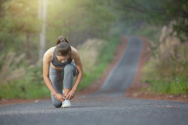 女性ランナーの実行中に彼女の靴を結ぶ