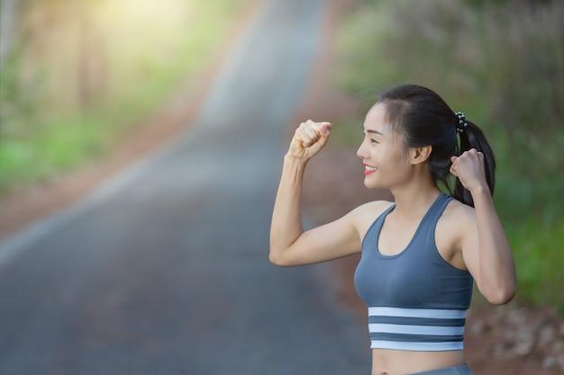 Женщина в спортивной одежде показывает бицепс