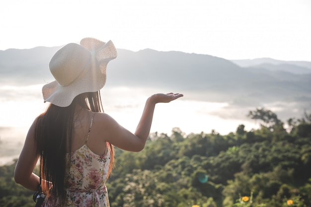 山の空きスペースで手を上げる女性