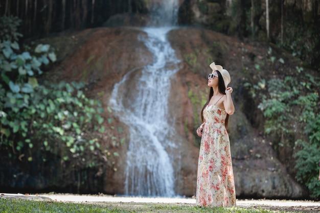 Красивая женщина в платье у водопада
