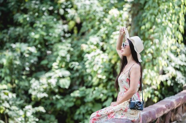 公園の手すりの上に座って幸せな女