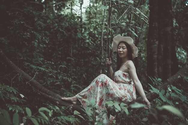 幸せの公園で麦わら帽子を着ている美しいアジアの女性