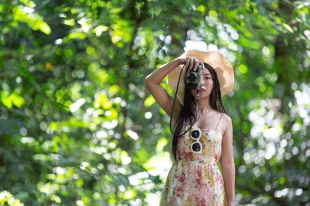 美しいアジアの女性は公園で写真を撮る