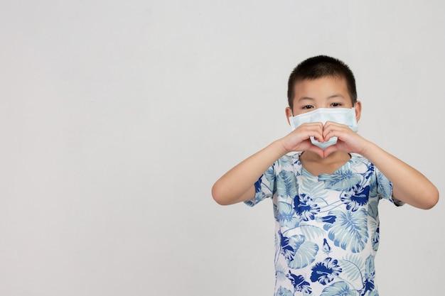 Мальчик в маске позирует на белом фоне