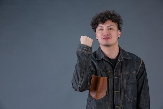 Человек показывая жест рукой в студии за представлять