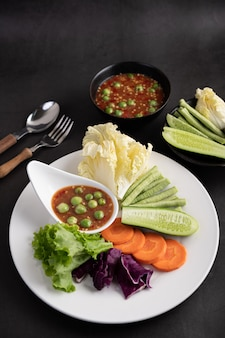 Креветочно-пастообразный соус в миске на белой тарелке с огурцом, двориком, тайским баклажаном, жареной белокочанной капустой, морковью и салатом