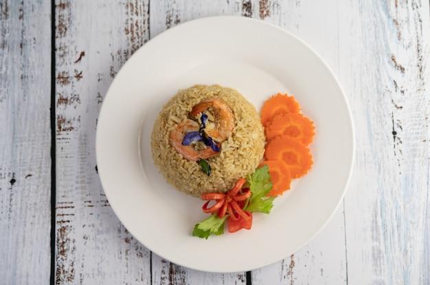 Жареный рис с креветками на белой тарелке, состоящей из помидоров и моркови.