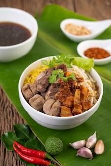 サクサクした豚肉、ポークのスライス、ミートボールと一緒にカップに入れた黄色の麺とタイ料理スタイルの麺