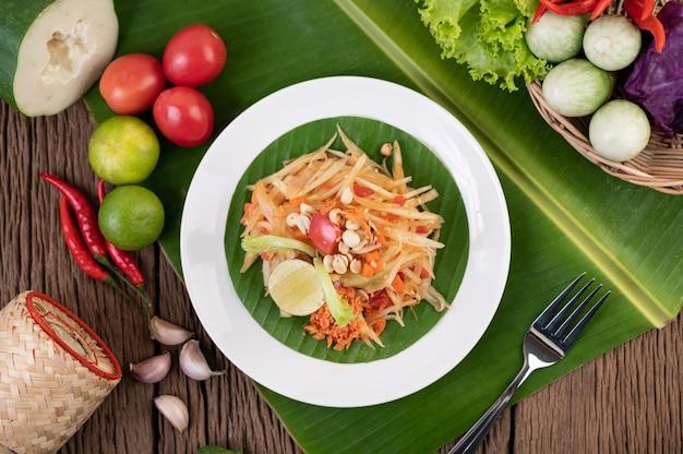 Тайский салат из папайи в белой тарелке на банановых листьях с лаймом, помидорами, баклажанами, чили, чесноком, перцем, салатом и арахисом.