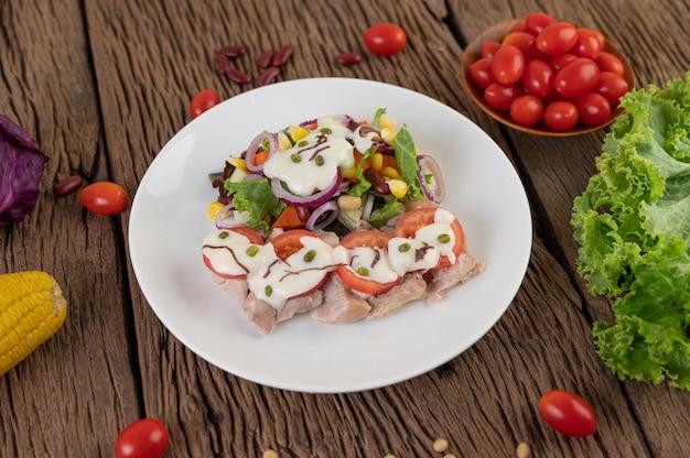 Фруктовый и овощной салат на белой тарелке на деревянном полу