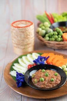 Паста из чили пасты в миске с баклажанами, морковью, чили, огурцами в корзине на деревянном столе