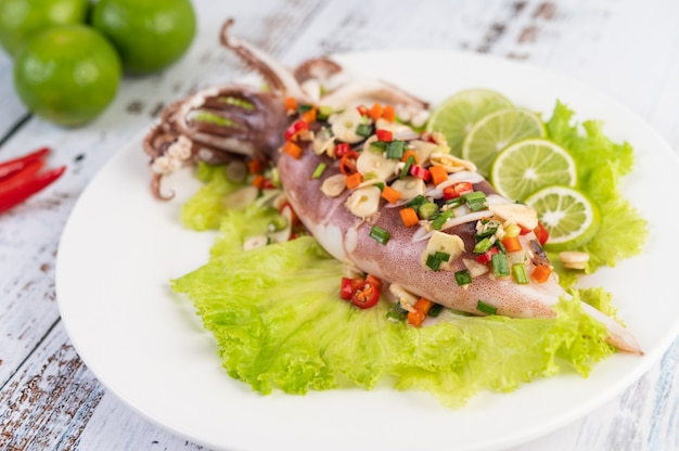 Острый лимонный кальмар с галангал, чили, морковь, мята перечная, зеленый лук и чеснок на тарелку на белый деревянный пол.