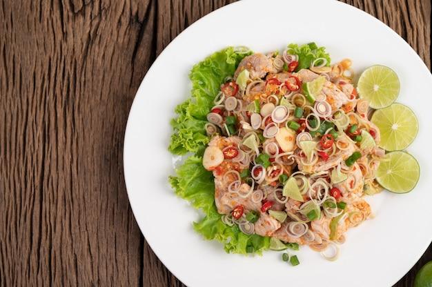 Острый салат из свинины с галангалом, лимоном, чили, чесноком и положить в салат на белой тарелке.