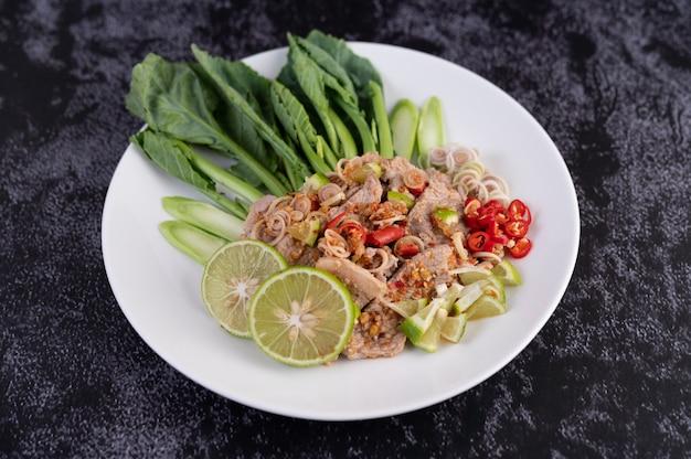 Острый салат из свинины с лаймом, капустой, галангалом, чили и чесноком в белой тарелке на черном цементном полу.